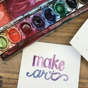 """A messy paintbox with a note: """"make art"""""""