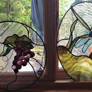 Two window panels, a bunch or grapes and a dragonfly