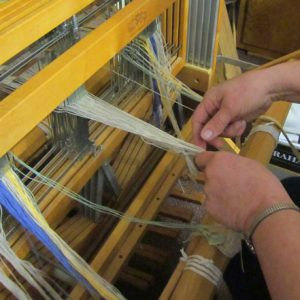 Photo of hands working with the threads on a loom