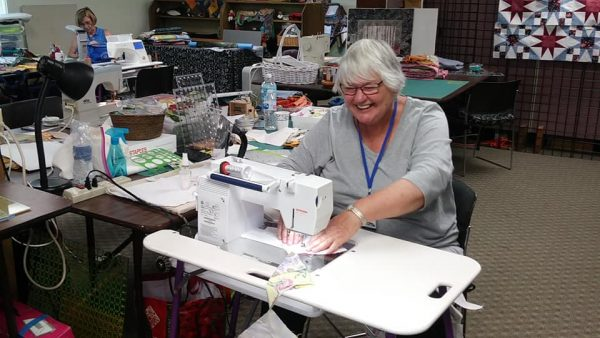 Smiling woman behind a sewing machine